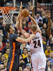 Golden State Warriors center Andrew Bogut, left, and Draymond Green, right, defend a shot from Portland Trail Blazers center Mason Plumlee, center, during the first half of an NBA basketball game in Portland, Ore., Friday, Feb. 19, 2016.