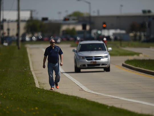 Tim Lee-Wasson of Howard walks along Lawrence Drive in De Pere. He works at Humana. The city will install sidewalks along the 2½-mile stretch of Lawrence Drive from Scheuring Road to its southern border, just south of Southwest Park.