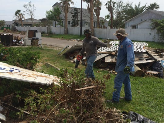 Michael Campbell (left) and Hugo Gomez haul debris away from a house in Port Aransas damaged by Hurricane Harvey.