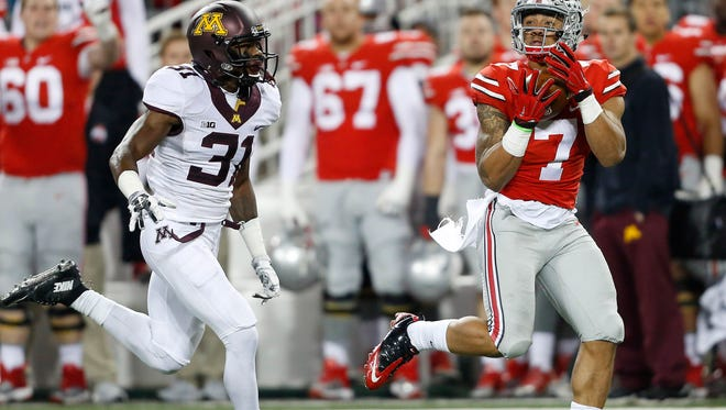 Ohio State's Jalin Marshall (7) hauls in the long pass in front of Minnesota Golden Gophers defensive back Eric Murray (31) during the second quarter at Ohio Stadium.