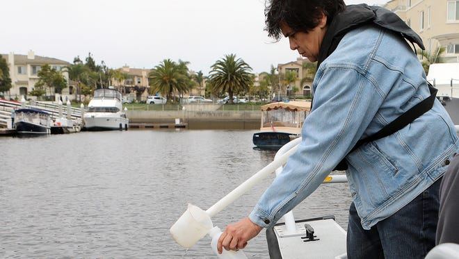 Oxnard Public Works Director Rosemarie Gaglione takes a water sample from the Channel Islands Harbor on Thursday.
