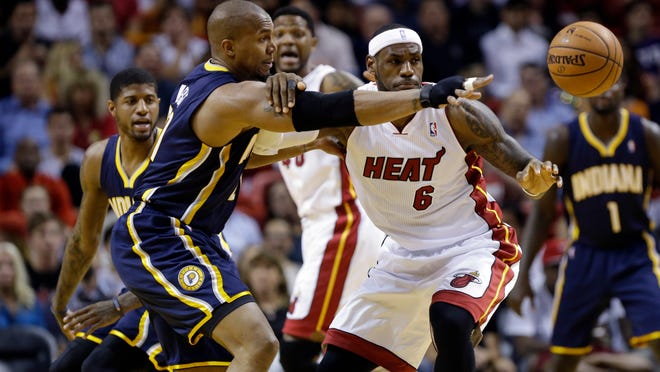 Indiana's David West (left) and Miami's LeBron James battle for a loose ball during a game in April.