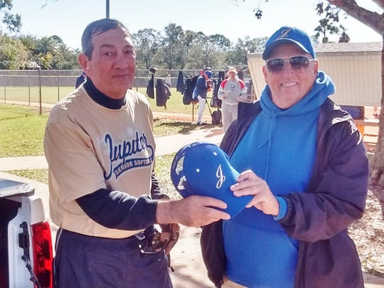 Gerry  Elias, at left, receives a hat from John Katulak during a recent practice session of the Jupiter Senior Softball Association.