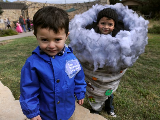 """Cannon Palacios, 2, and his 5 year-old brother Caliber came to Boo at the Zoo on Saturday as a weatherman and a tornado. """"Caliber loves tornadoes,"""" said his mother, Amanda. """"He has been saying he wants to be one since last time."""" Amanda and her husband Raul completed the group costumes by both wearing T-shirts with """"storm chaser"""" written on it."""