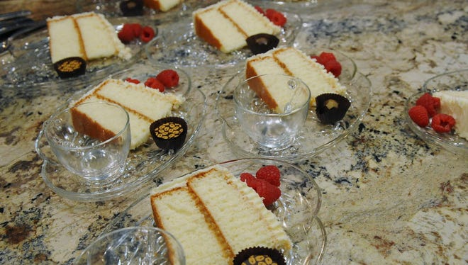 Dessert—Lemon Lovers' White Chocolate Cake--is plated with raspberries and local chocolates.