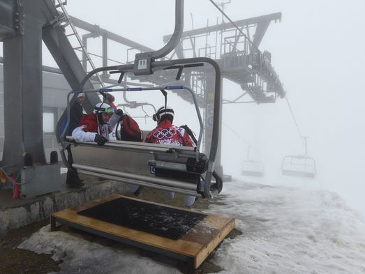 Kevin Hill (CAN, left) and Robert Fagan (CAN, right) head down on a ski lift during a weather delay for men's snowboardcross.