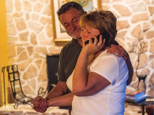 Emanuel Skarlatos holds his wife, Karen, while she speaks to a reporter from France on Friday night in their Roseburg home.
