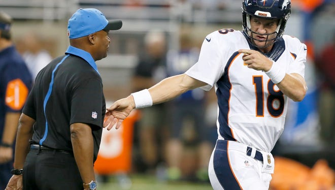 Broncos quarterback Peyton Manning makes one last point to Lions coach Jim Caldwell as they finished their conversation at midfield before the Lions' loss Sunday at Ford Field.