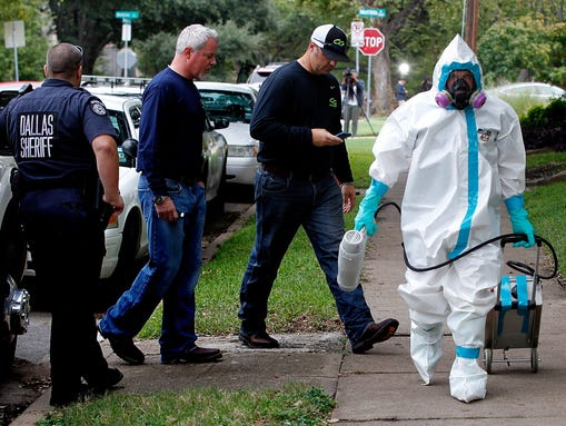 A man dressed in protective clothing leaves after treating