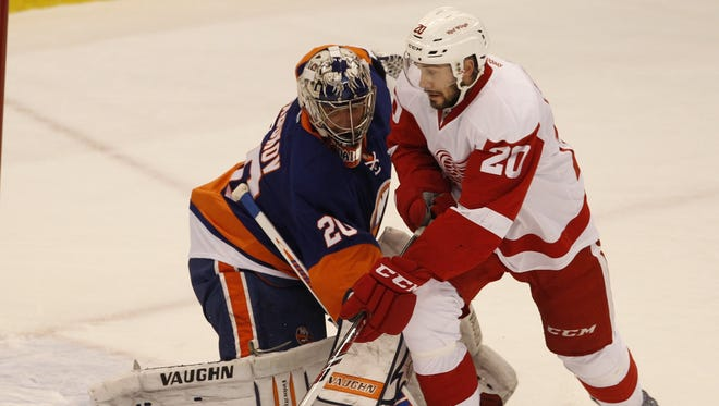 Detroit Red Wings forward Drew Miller, right, tries to get his stick on the puck in front of New York Islanders goalie Evgeni Nabokov on Dec. 23,  2013.