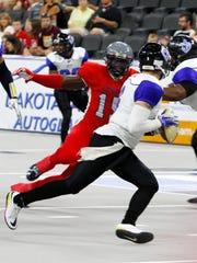 Sioux Falls Storm defensive lineman Claude Davis pursues Cedar Rapids Titans quarterback Dylan Favre.
