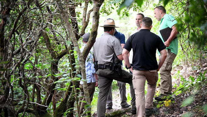 Investigators stand along the trail July 26 where a woman's body was found Tuesday.