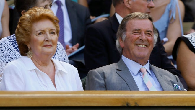 British presenter Terry Wogan and his wife Helen prepare to watch a match at the All England Lawn Tennis Championships in Wimbledon on July 3, 2015.