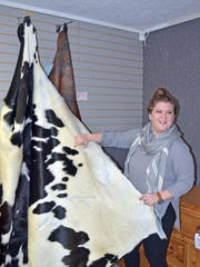 Store employee Ashley Smith talks about the cowhide rugs available at the Southern State Rustic Furniture and Accessories store located at 646 Ridgewood Road in Ridgeland.