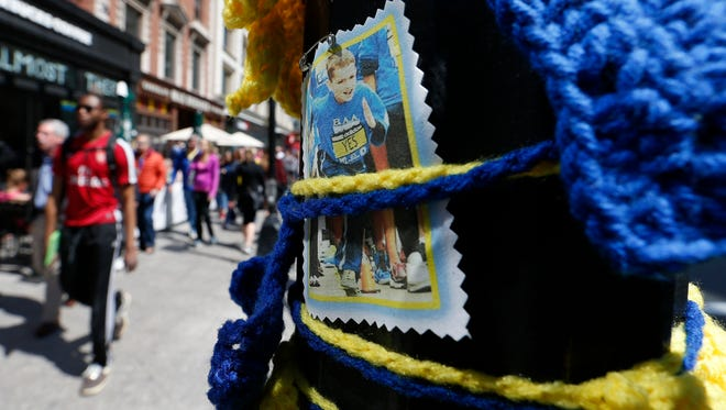 Pedestrians pass a photograph of Boston Marathon bombing victim Martin Richard, April 18 in Boston, at the spot where the second bomb detonated at the marathon in 2013.