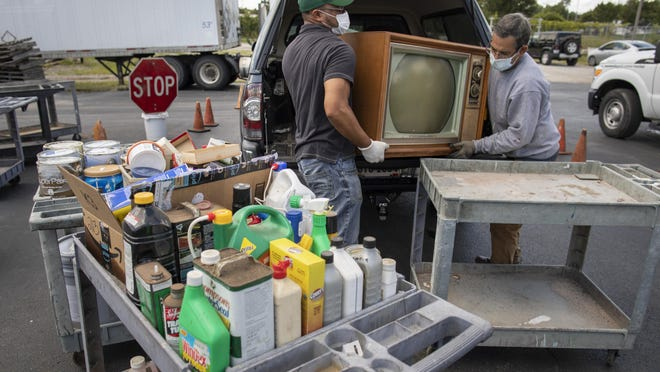 Jose Castillo, left, and Juan Mondeja unload paints, cleaners and an old television, which could have as much as 10 pounds of lead in its tubes, at the SWACO Household Hazardous Waste Drop-Off Center in the Milo-Grogan neighborhood. The disposal service is free, with the exception of a few items, for Franklin County residents.