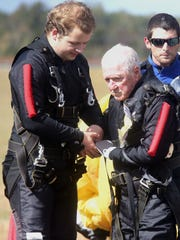 Alex Nixon, left, helps his great-grandfather Robert Allman get adjusted after Alllman parachuted from an airplane, on Oct. 21, 2016, one day after turning 100.
