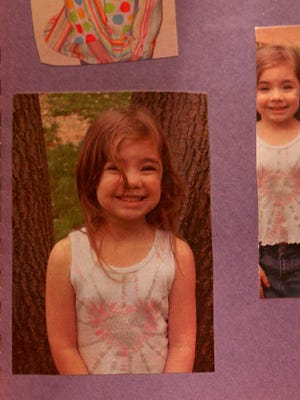 A childhood photo of Lauren Landavazo is shown from a scrapbook. Her parents described her as a child that constantly smiled and was always happy.