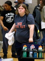 Oakland girls basketball manager Elizabeth Schott gathers water bottles during Tuesday's game at Siegel.
