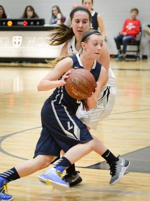 Lake Country Lutheran guard Katherine Benes drives past Living Word Lutheran spohomore guard Lily Kadubeck.
