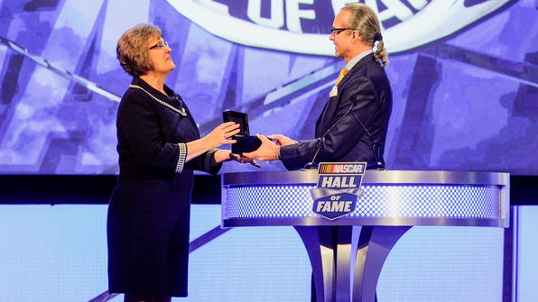 Former driver Kyle Petty presents the NASCAR Hall of Fame ring to a granddaughter of Raymond Parks, Patricia DePottey, during the NASCAR Hall of Fame induction ceremony in Charlotte, N.C., Friday, Jan. 20, 2017. (AP Photo/Mike McCarn)