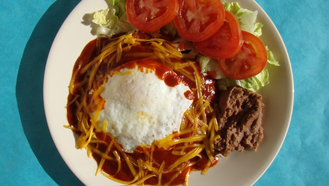 """An enchilada, something different to kick in 2016, just around the corner. My version, which I posed, shows an egg, making the tasty meal """"brunch."""" Plain cheese/onion red chile enchilada is the way to go and less work."""
