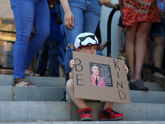 "A child holds up a ""Be Kind"" sign with a photo of Mr. Rogers on the steps of the Tom Green County Courthouse during a prayer vigil for immigrant families being separated  Monday, June 25, 2018."