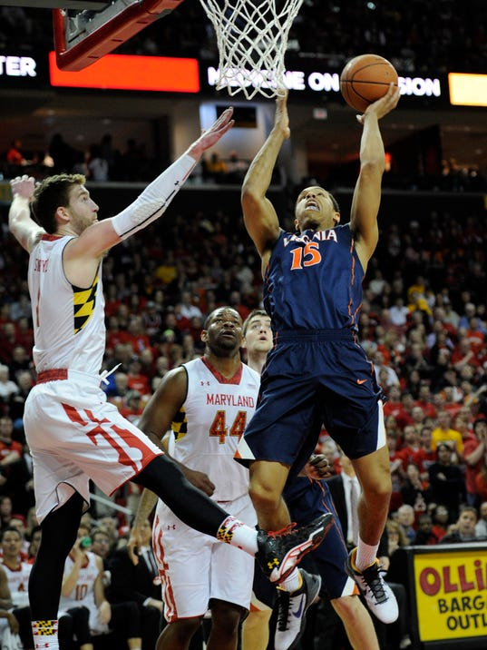 Virginia guard Malcolm Brogdon (15) goes to the basket against Maryland forward Evan Smotrycz during the first half of an NCAA college basketball game, Sunday, March 9, 2014, in College Park, Md. Also seen is Maryland center Shaquille Cleare (44). (AP Photo/Nick Wass)