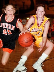 -Roosevelt's Krista Orsack (right) and Huron's Cori Vining chase a loose ball during the second half of Friday night's Class AA semifinal game at the Corn Palace in Mitchell.