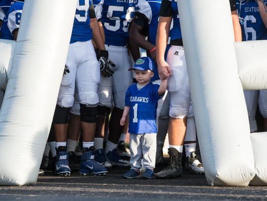 Eli Tadli, 3, waits with Stephen Decatur football players