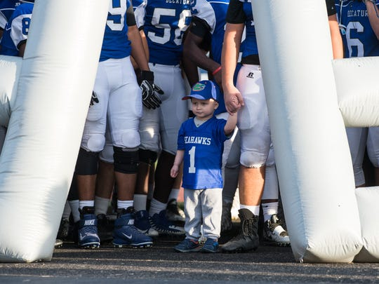 Eli Tadli, 3, waits with Stephen Decatur football players before entering the field on Friday, Sept. 22, 2017.