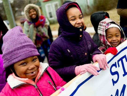 Children carry a banner during the annual MLK Memorial