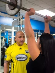 Fitness trainer Johnny Jimenez coaches client Stefanie Hernandez on the use of barbells at Las Cruces Fitness Center.