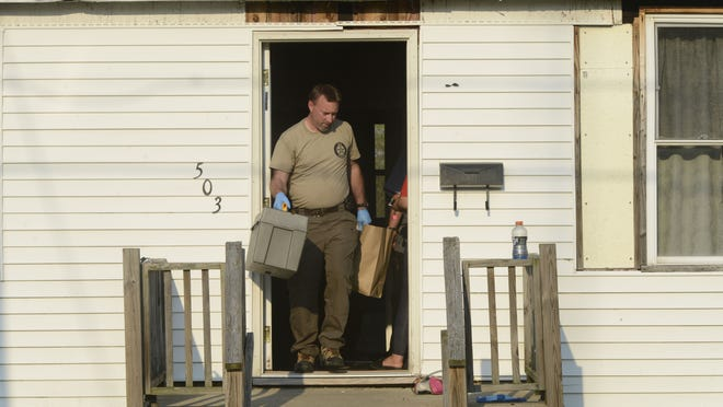 The Ohio Bureau of Criminal Investigation removes items from a home at 503 Bidwell Ave. in Fremont.