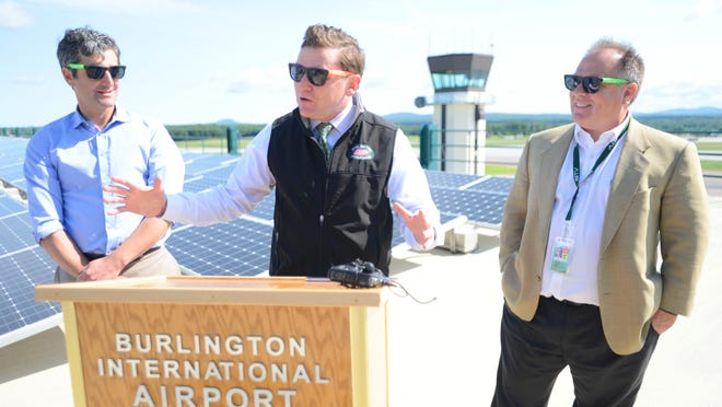 Burlington Electric Department General Manager Neale Lunderville details a new 500-kilowatt solar array on the roof of the Burlington International Airport parking garage Thursday morning. He is flanked by Burlington Mayor Miro Weinberger, left, and Gene Richards, the airport's director of aviation.
