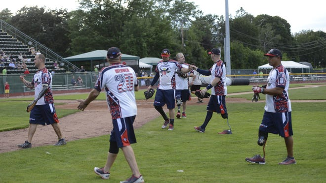 Members of the Wounded Warriors Amputee Softball Team walk off the field during the game.