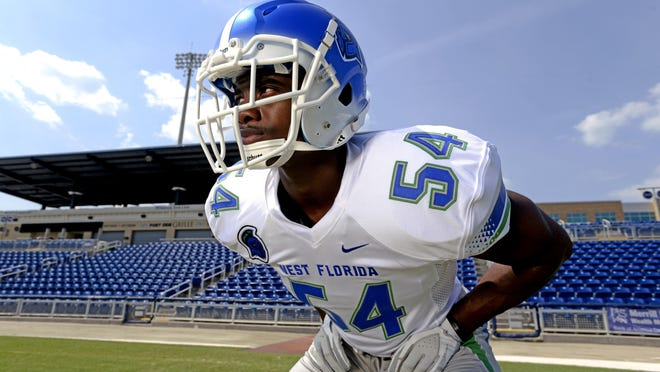 Jamie Smith, a freshman linebacker and former West Florida High star, models UWF's away uniform during a recent photo shoot at the Blue Wahoos bayfront stadium.