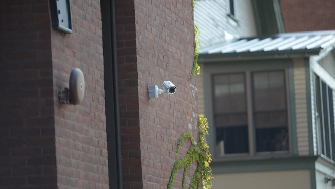 A security camera films pedestrians and cars on Pearl Street at Elmwood Avenue in Burlington.
