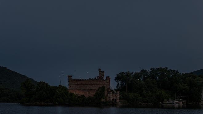 """Artist Melissa McGill's """"Constellation"""" art installation glows at night above Bannerman Castle on Pollepel Island in the Hudson River in Beacon. McGill said the installation is a constellation of stars but also a constellation of people and organizations that made it happen."""