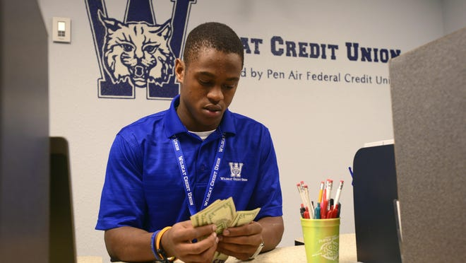 Teller Tyree Jackson makes a cash withdrawl for fellow student David Reynolds on Friday at the Washington High School Wildcat Credit Union. Jackson and Dima Yousef, center, are part of the Marketing and Enterprising Academy, one of several Escambia County School District's Workforce Education department Career Academies that prepare students for the workforce.