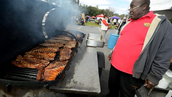 Denby Williams with Arlene Williams Bar-B-Que checks on some ribs during a previous Smokin' in the Square. The festival returns to Seville Square this weekend.