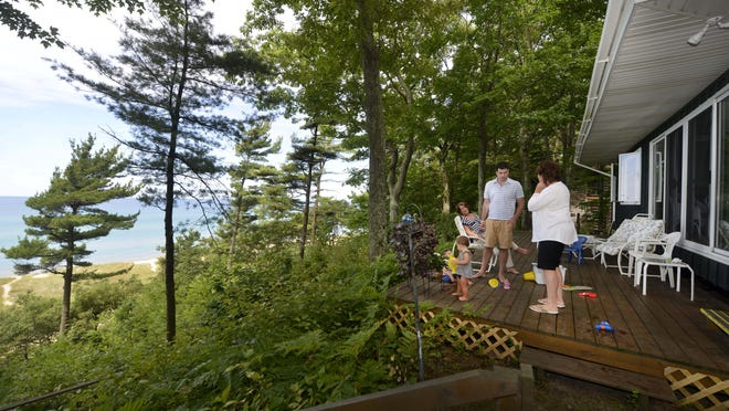 Above: Trevor MacMeeken and his children, Cal and Lucy, enjoy time at their cottage with his mother, Colleen Mac Meekin, and aunt, Cathy Houlihan. The New Era house was built by their parents and has been in the family for decades. Right: The state partially denied a tax break for Dick and Betsy DeVos' $7.8 million compound in Ada Township.