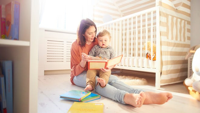 young mother reading a story to her toddler in his bedroom