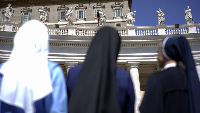 FILE - In this Monday, April 21, 2014 file photo, nuns look up at Pope Francis delivering his blessing during the Regina Coeli prayer he celebrated from the window of his studio overlooking St. Peter's Square, at the Vatican. Advocates of women's ordination as Roman Catholic priests are citing the church's unfolding sex abuse scandals in mid-2018 as powerful arguments for their cause, while acknowledging, as they do so, the high unlikelihood of achieving their goal any time soon. (AP Photo/Andrew Medichini)