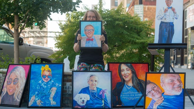 Local artist Becky Drager sits between a collection of paintings Wednesday she's recently completed of Topeka leaders and community members. Drager will be showing the full collection from 11 a.m. to 7 p.m. Oct. 10 at the NOTO Arts Center.