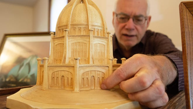Duane L. Herrman, author and local leader in the  Baháí faith, explains the scale of a model of the Bahá'í House of Worship in Wilmette, Ill. Friday afternoon at the Topeka Friends Meeting place at 603 SW 8th St.