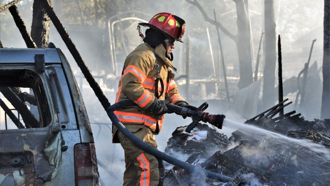A Bastrop firefighter douses a fire Sunday afternoon that spread from a person burning debris at 281 Lake Bastrop Acres Drive, fire officials said.