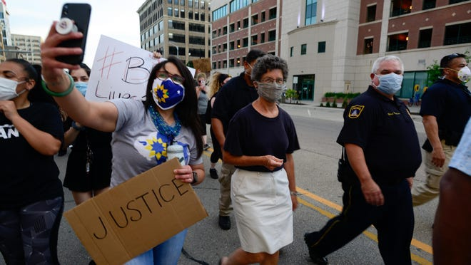 Topeka Mayor Michelle De La Isla, left, takes a selfie while marching with Councilwoman Karen Hiller, middle; Topeka Police Chief Bill Cochran, right; and Lt. Manuel Munoz, far right, during a peaceful protest Monday through downtown Topeka. The protest was in response to the death of George Floyd on May 25 at the hands of Minneapolis police.