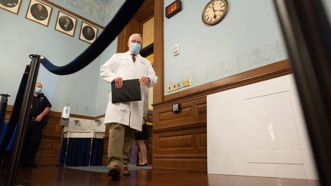 """Lee Norman, Kansas secretary of health and environment, enters a news conference Wednesday afternoon in the Statehouse to give updates on COVID-19 cases in Kansas. """"We are in the first quarter,"""" Norman said in comparing the pandemic to a football game."""