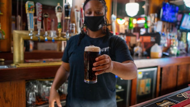 Latasha Lake, bartender at the Celtic Fox, serves up beer Tuesday afternoon.